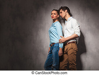 side view of a young casual couple looking away