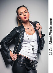 young blonde woman in leather clothes pulling her collar