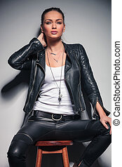 sexy woman in leather clothes holding hand behind her neck