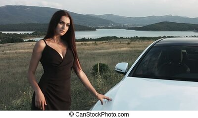 Two sexy young women in beautiful evening gowns standing near the the white car