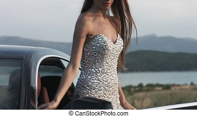 Gorgeous girl with long hair in the dress with rhinestones...