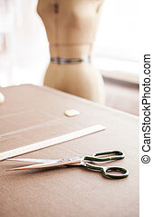Still life photo of a suit pattern template with tape measure, chalk and scissors. Sewing tools and accesories.