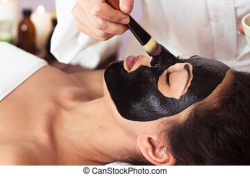 Prettyl woman with facial mask at beauty salon. Spa...