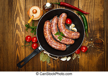 Top view of pork sausages in frying pan