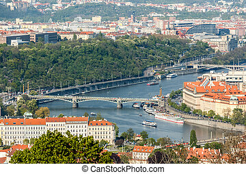 Aerial view of Prague with bridges and ships on Vltava...