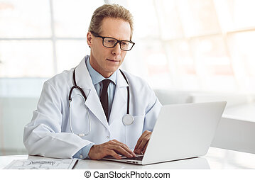 Handsome mature doctor in eyeglasses is using a laptop while...
