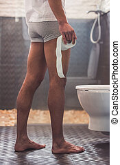 Afro American man in toilet - Cropped image of handsome Afro...