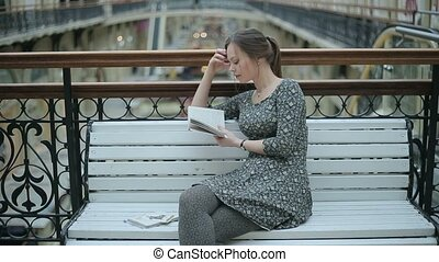 Young girl reading a book on bench