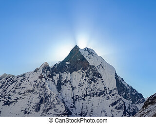 Mountain peak and rays of rising sun from behind him -...