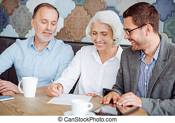Cheerful aged couple signing the contranct - Put your...