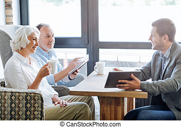 NIce smiling aged couple having meeting in the cafe - Ensure...