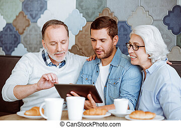 Positive man and their grandparents resting in the cafe -...