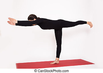 Beautiful athletic girl in black suit doing yoga....