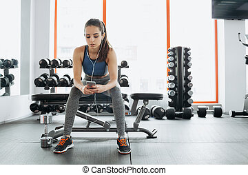 Young woman with earphones listening to music after hard workout in gym.