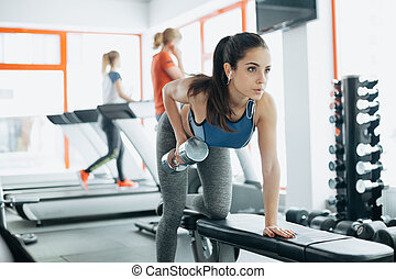 Young beautiful woman doing exercises with dumbbell in gym....