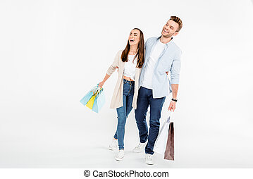 couple with shopping bags embracing and looking away on white