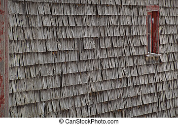Old weathered cedar shakes shingles barn with red window