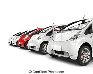 Compact white electric cars in a row - red stands out