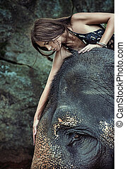Brunette lady stroking an elephant - Brunette lady stroking...