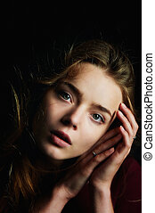 Beautiful girl looks piercing eyes into the camera. Hair...