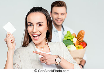 woman pointing to credit card in hand with man behind