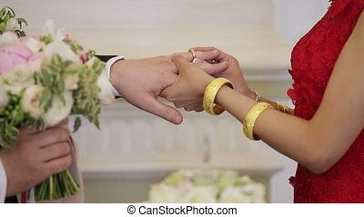 Bride puts a ring to grooms hand - Bride puts on a ring to...