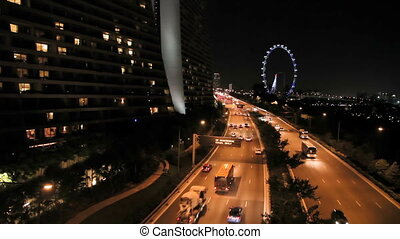 Road traffic in night. Cars with lit headlights going on the road. Singapore.