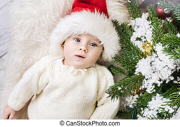 Relaxed little boy lying next to the pine