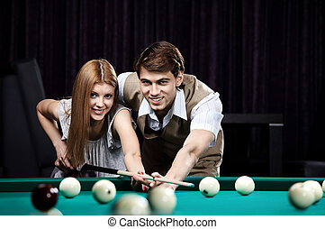 Happy couple in a billiard room - The young happy couple...