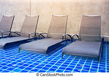Chaise lounges in swimming pool