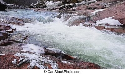 Winter mountain river flows in granite canyon