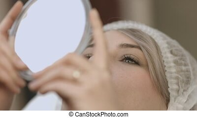 Patient looking at herself in the mirror after the lip...