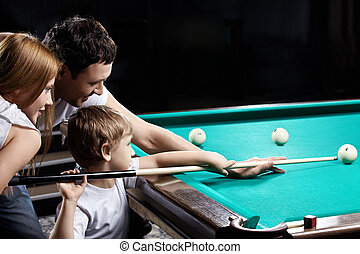 The family plays billiards - The young couple and the child...