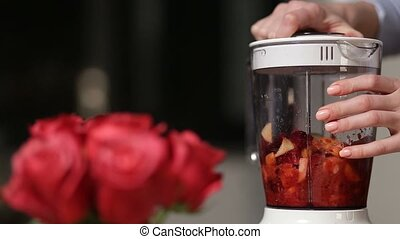 Woman blending food ingredients to make smoothie - Closeup...