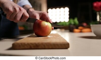 Woman with knife cutting apple on chopping board