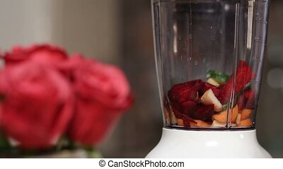 Woman adding vegetables and fruits into blender - Closeup...