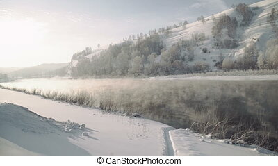 Mountain river in the early morning. Steam rises over the...