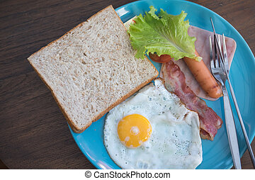 Breakfast with egg ham sausage and bread on blue plate