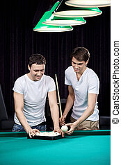 The players - Two young men put spheres for billiards