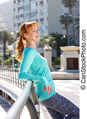 smiling female athlete leaning on railing outside in the city