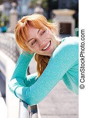 happy female athlete leaning on railing outside