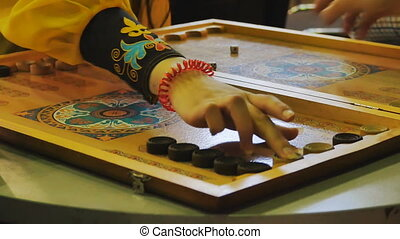 man and woman playing backgammon