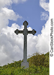 stone cross against in the blue sky