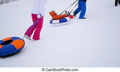 the family rises to snowy hill with snowtube. slow motion. snow winter landscape. Active rest, sports