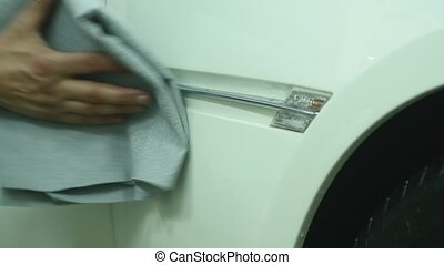 A man cleaning car with microfiber cloth - auto detailing service concept