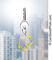 Silver key with house shape keyring, on city buildings...