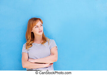 thinking woman standing with arms crossed by blue wall