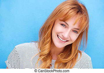attractive redhead woman laughing by blue wall - Close up...