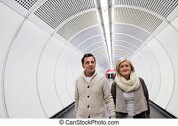 Senior couple in winter clothes walking in hallway of subway
