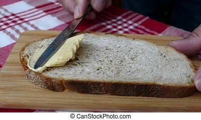 Butter being spread on a bread slice